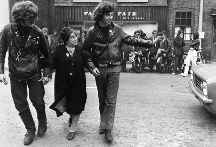 Hell's Saints bikers help an old lady across the road, August 1970.