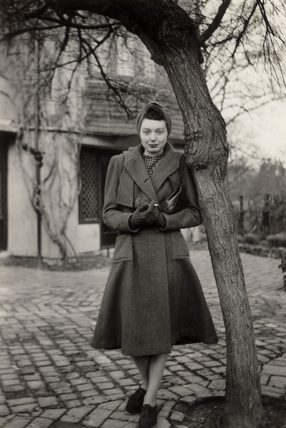 Woman standing beside a tree, 1940s.