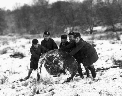 Schoolboys rolling a giant snowball, c 1930.