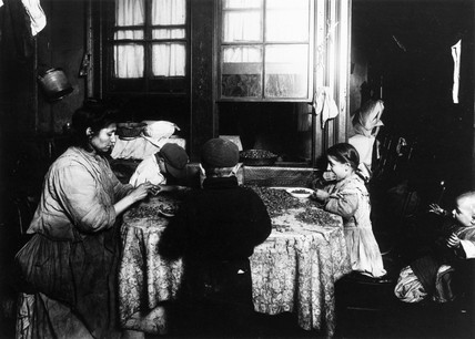 Immigrant mother and her children shelling nuts, New York, c 1908-1918.