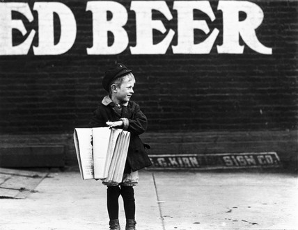 Young newsboy in front of a saloon, USA, 1910.
