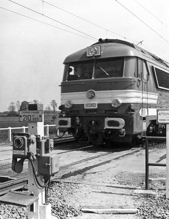 Electric train going over a level crossing, France, April 1968.