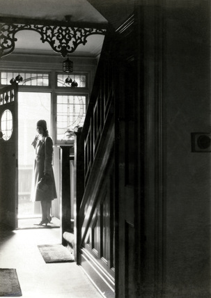 Woman at the front door, England, 1920s.