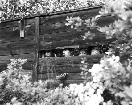 Spectators watching a motor race through a gap in the fence, Berlin, 1932.