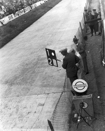 Mechanic holding pit signalling boards on a motor racing track, Germany, 1932.