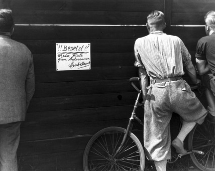 Men watching a motor race through a gap in a fence, Berlin, 1930s.