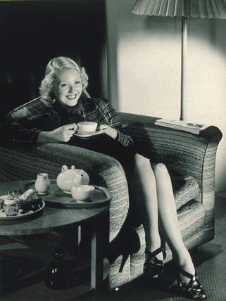 Woman with tea and cakes, c 1940s.