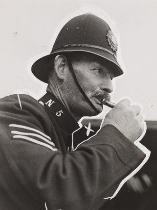 A policeman blowing a whistle, 1938.