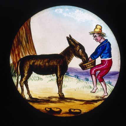 A basket of food is offered to a donkey. Ha
