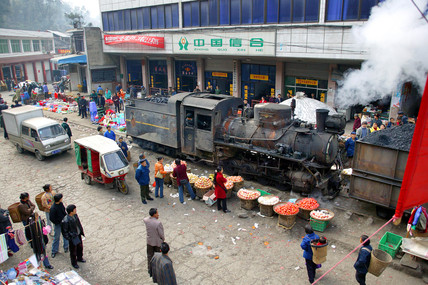 A Weiyuan Railway coal train running through Huangjingou market, Gansu province, China