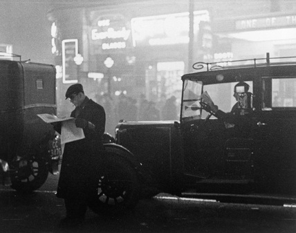 Taxis queueing in traffic during bad fog in central London, 1934. Photograph by James Jarche (1891-1965).