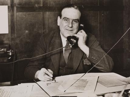 Gordon Helsby, newspaper editor, on telephone in office.