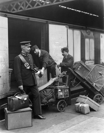 Porters loading luggage into the baggage van of a London & North Western Railway train to Greenore.