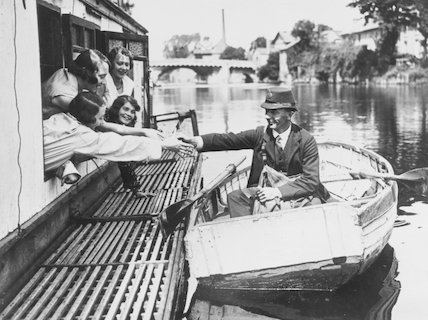 Postman delivering the mail by rowing boat, 31 July 1930.