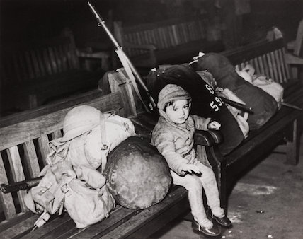 Small child sitting on a bench with soldiers' equipment, 28 December 1939.