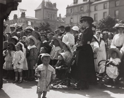Young boy looking miserable as behind him a crowd of children watch a Punch and Judy show, c 1900s.