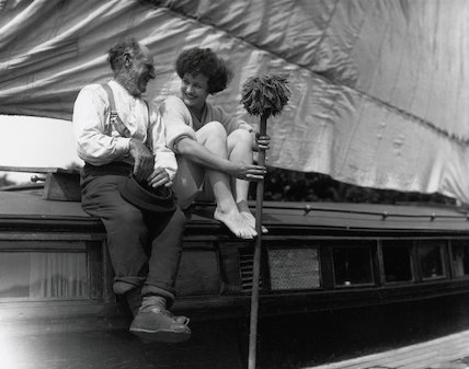 Couple with mop sitting on a barge, c 1920s.