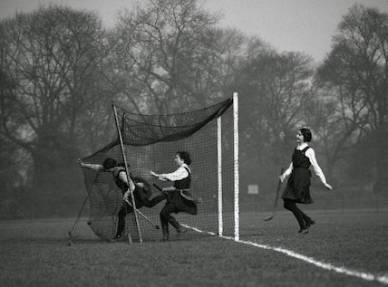 Schoolgirls crashing into a goal net during a hockey match, c 1920s.