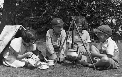 Four children enjoying a tea party in the garden, c 1920s.