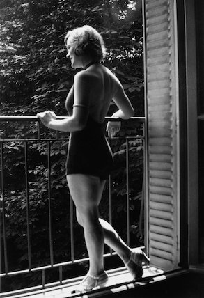 Young woman in a bathing costume looking out from a balcony, c 1920s.