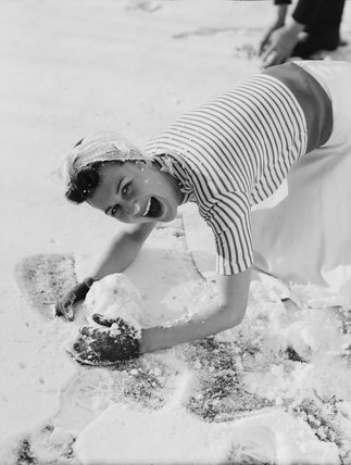 Woman rolling a snowball c1930s.