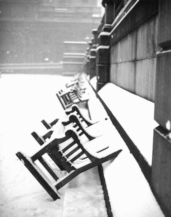 Benches in snowy Trafalgar Square, London.