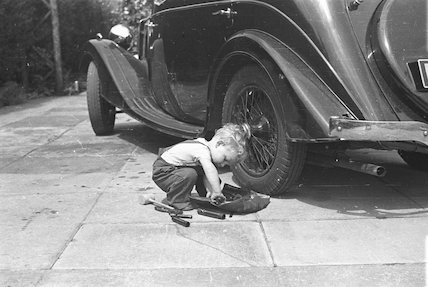 Young child making adjustments to the rear wheel of a Riley saloon car, c1930s.