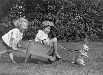 Two children playing with a wheelbarrow harnessed to a toy rabbit, c.1930s.