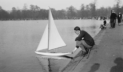 Man releasing a model boat onto a pond c.1930s.