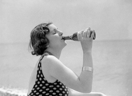 Woman in a bathing costume drinking Schweppes by the sea, c 1920s.