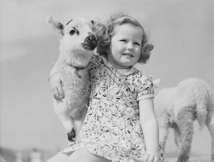 Young girl cuddling a lamb.