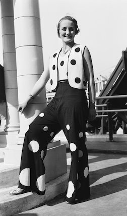 Woman modelling a polka dot trouser suit, c 1930s.