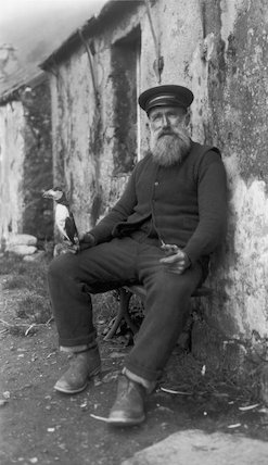 Bearded fisherman holding a stuffed puffin and a pipe, c 1910s.