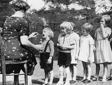 Evacuees queueing to take medicine c. 1939.