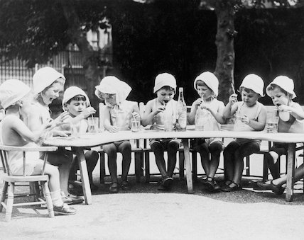 A group of young infants sat around a table outside drinking.
