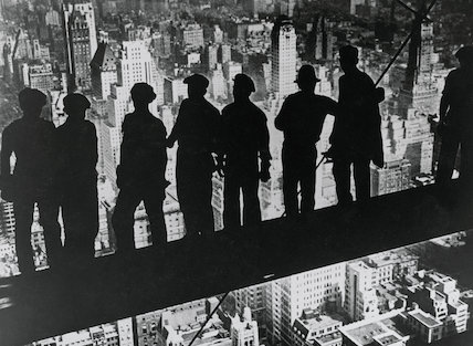 Black and white photograph of steel workers silhouetted against the New York skyline, 27 December 1938.