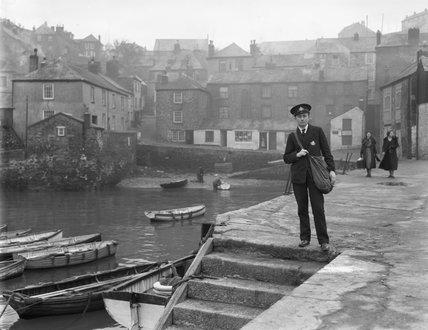 Postman standing at quayside, Polruan - 1935