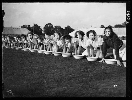 Women ducking for apples