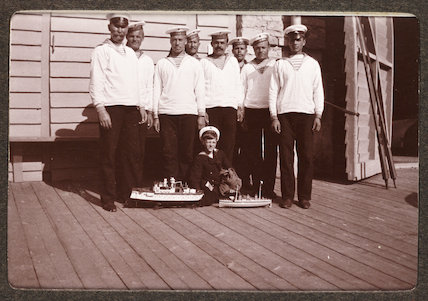 Russian snapshot album: sailors and a boy with model ships, c.1915