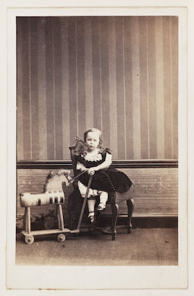 A carte-de-visite portrait of a young girl with her toy horse, taken by an unknown photographer in about 1865.