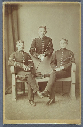 Carte-de-visite of three soldiers, two seated and one resting against the studio bench.