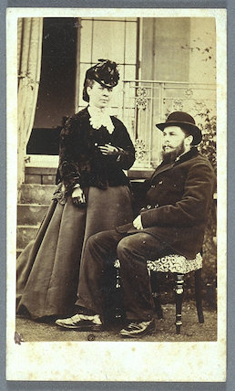 Carte-de-visite of a couple, unusual for the man to be seated and woman standing in the dominant pose.