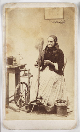 A carte-de-visite of a woman working at a spinning wheel, taken by an unknown photographer in about 1870.