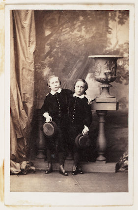A carte-de-visite portrait of two young boys, possibly twin brothers, taken by an unknown photographer in about 1865.