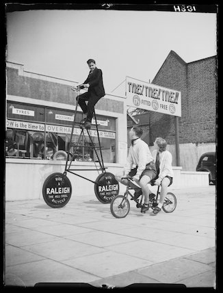 Cyclists riding unusual bicycles, 1939
