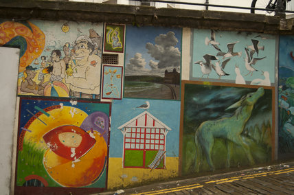 A collage of The Blands Cliff Murals on brick wall