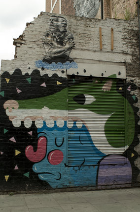 Graffiti in East London of green fox and man shaking