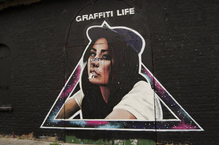 Graffiti in East London of girl surrounded by triangle with the words Graffiti Life