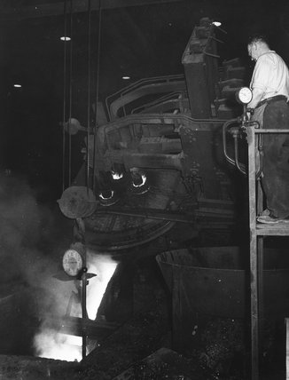 Works photographic negative showing steel foundry employee filling furnace, 1945.