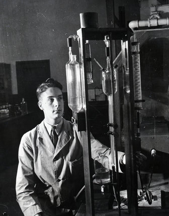 Works photographic negative showing laboratory employee conducting a carbon test, 1945.